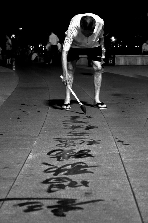 Old Man Practicing Calligraphy on the Sidewalk in Park plaza